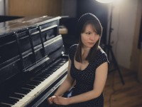 Portrait. A pianist and songwriter sits at her piano and stares behind her illuminated by soft light