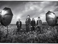 Portrait. Triggered flashes illuminate a band posed in a rapeseed field finished in black and white.